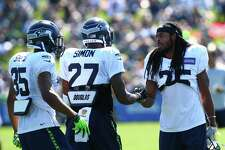 Richard Sherman, right, greets Tharold Simon (27) and DeShawn Shead (35) during day five of the Seahawks mini camp, Thursday, Aug. 4, 2016 at Virginia Mason Athletic Center.