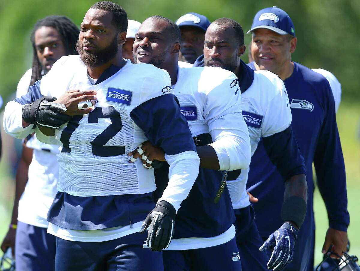 Cliff Avril leads an agitated Michael Bennett (72) away from a scuffle he got into during day five of the Seahawks mini camp, Thursday, Aug. 4, 2016 at Virginia Mason Athletic Center.