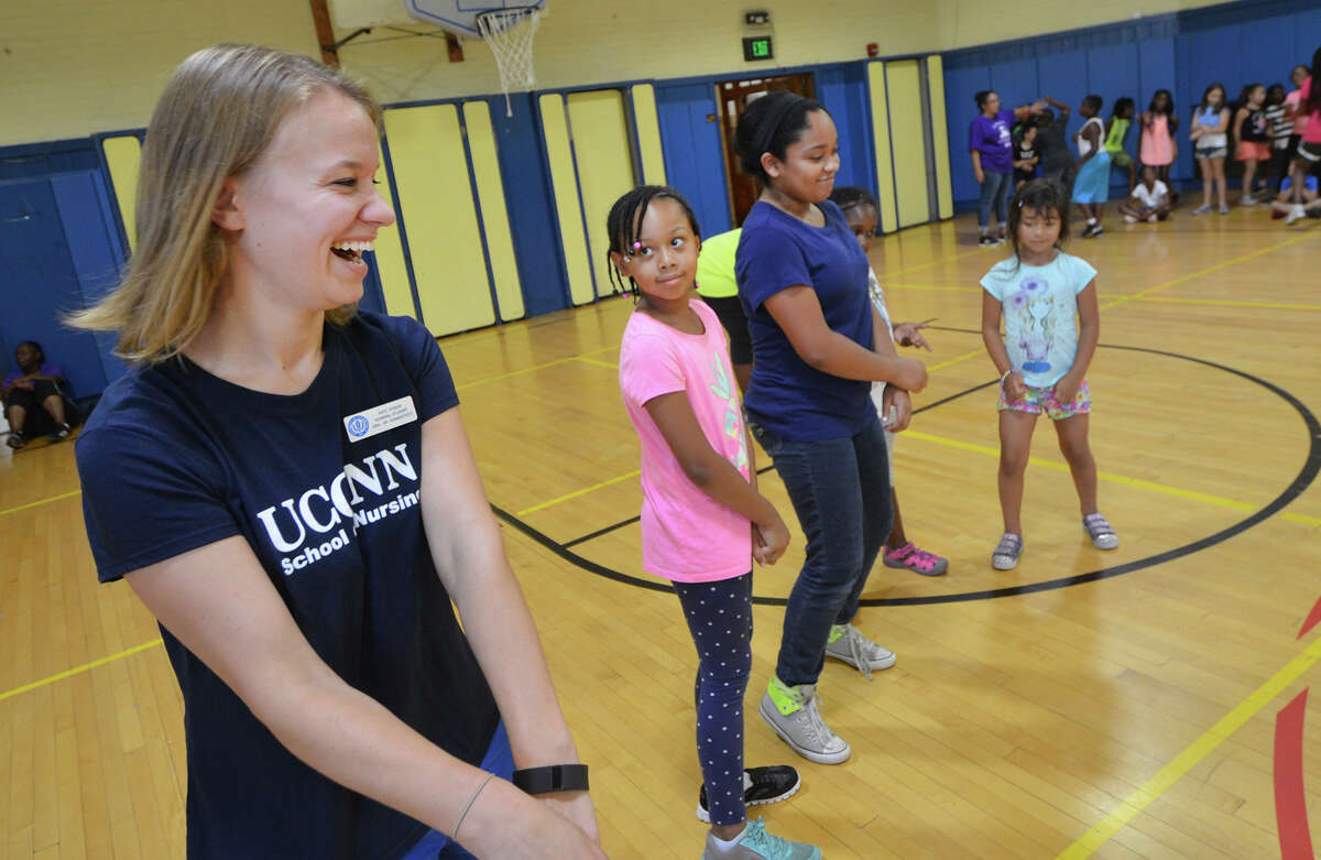 Kate Kosior with the University of Connecticut School of Nursing dances with the few remaining campers in the ACHIEVE summer camp program at Tracey School during a round of Freeze Dance on Thursday.