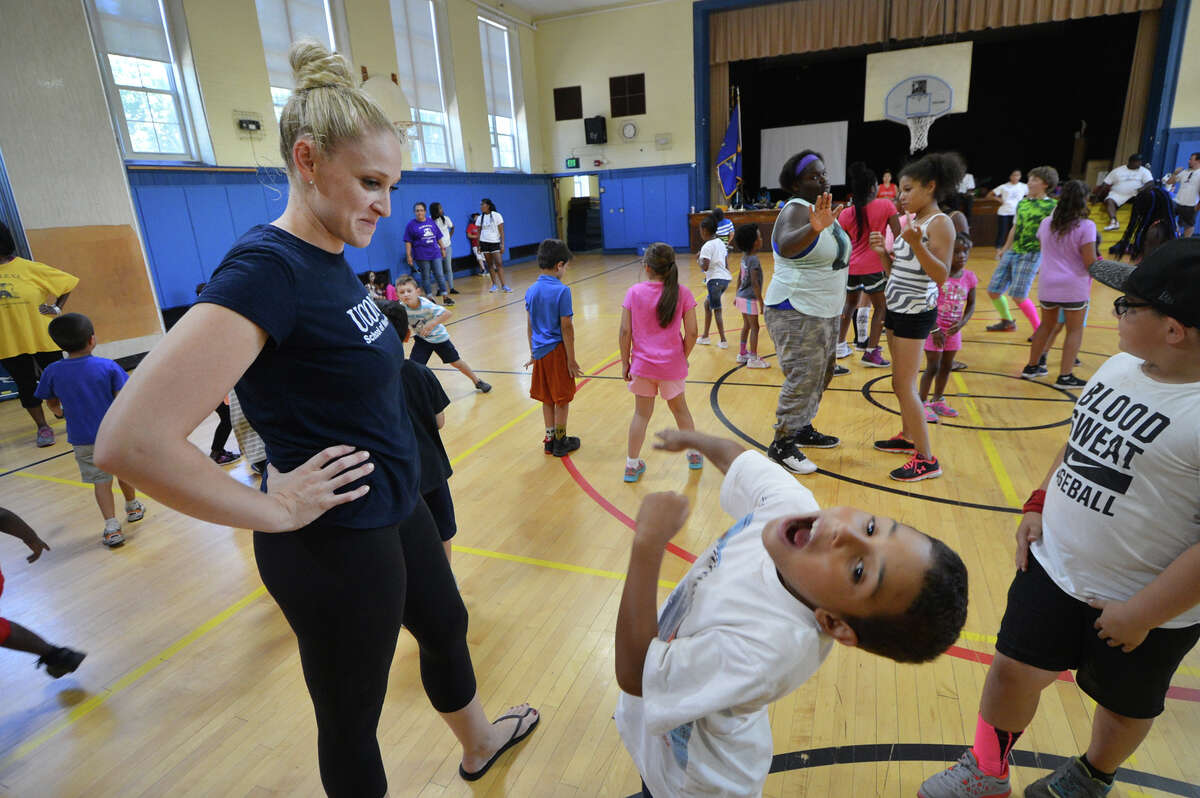 Megan Crouch with the University of Connecticut School of Nursing watches as the music stops and so do the kids, in the ACHIEVE summer camp program at Tracey School during a round of Freeze Dance on Thursday.