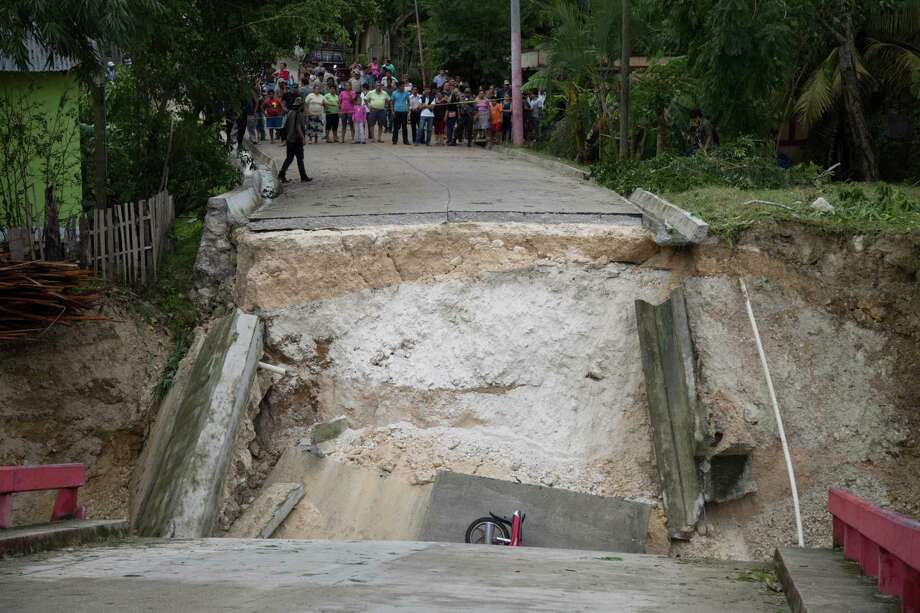A motorcycle is stuck in the debris of a collapsed bridge brought down by Hurricane Earl in Melchor de Mencos, Guatemala, near Belize. Earl dumped as much as 12 inches of rain over parts of Guatemala. Photo: Luis Soto, STR / Copyright 2016 The Associated Press. All rights reserved. This material may not be published, broadcast, rewritten or redistribu