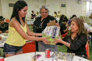 Alma Morales (right) receives a prize from Sylvia Davila, 17, as Juanita Reyna looks on after winning a game of loteria during a fundraiser for Fuerza Unida's summer youth leadership program.