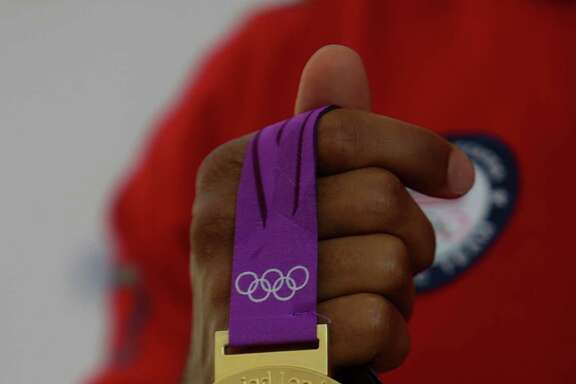 Olympic wrestler Jordan Burroughs holds the gold medal he won at the 2012 London Olympics as he poses for a picture while waiting to board his flight to Rio at Bush Intercontinental Airport, Wednesday, Aug. 3, 2016, in Houston. United is a sponsor for Team USA and expects to fly 1300 athletes, coaches and team staff to Rio for the Olympic and Paralympic games. ( Mark Mulligan / Houston Chronicle )