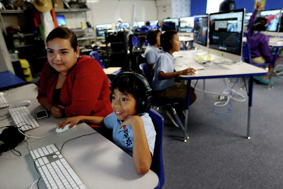 The technology room is teeming with activity at KIPP Explore Academy in Houston. Paraprofessional Lorena Galvan helps 7-year-old Carlos Muñoz, a second-grader in May. Photo: Gary Coronado, Staff / © 2015 Houston Chronicle
