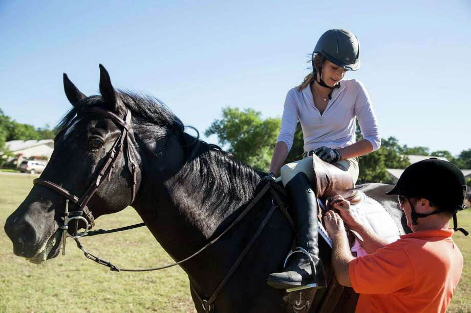 "Silas ""Jeeper"" Ragsdale adjusts Grace Kuenzel's girth while she got ready to ride Cash in a lesson at Camp Stewart for Boys in Hunt, Texas on August 4, 2016. Ragsdale is going to Rio de Janeiro to coach USA Pentathlon competitors in the riding component. He will have 15 minutes to help riders become acquainted with their Olympic-issued horses before they must compete. Kuenzel is hoping to qualify for the 2020 Olympic pentathlon team. Photo: Carolyn Van Houten /Carolyn Van Houten / 2016 San Antonio Express-News"