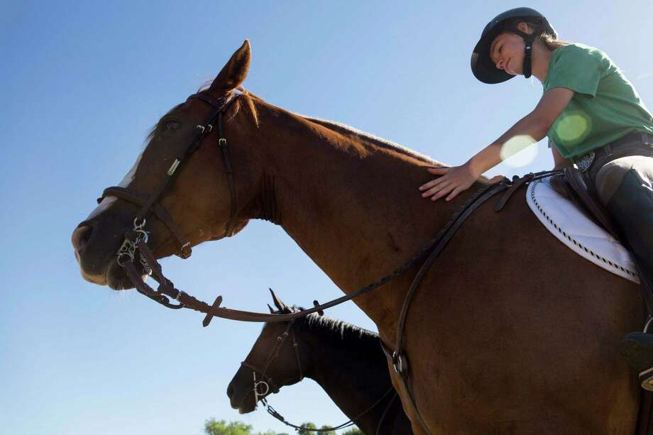 """Payton White pets Socks during a lesson with Silas """"Jeeper"""" Ragsdale at Camp Stewart for Boys in Hunt, Texas on August 4, 2016. Ragsdale is going to Rio de Janeiro to coach USA Pentathlon competitors in the riding component. He will have 15 minutes to help riders become acquainted with their Olympic-issued horses before they must compete. Photo: Carolyn Van Houten /Carolyn Van Houten / 2016 San Antonio Express-News"""