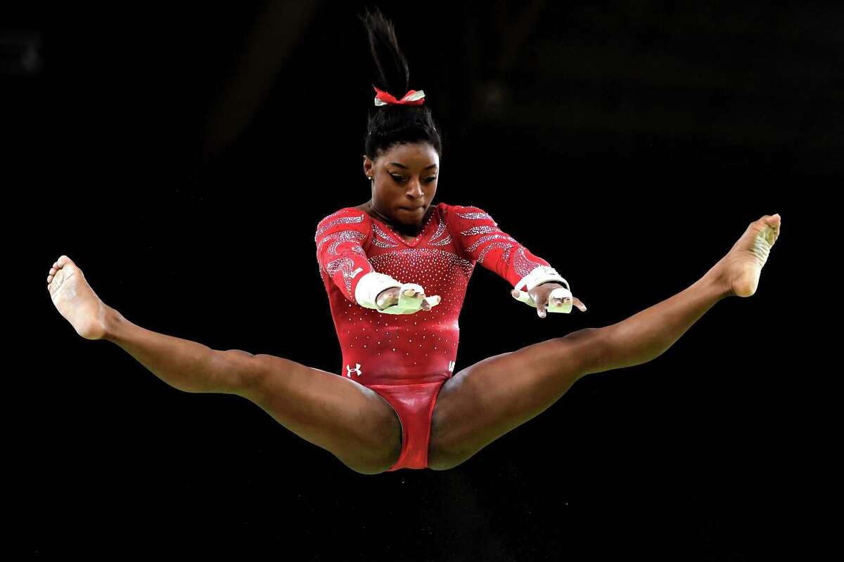 RIO DE JANEIRO, BRAZIL - AUGUST 04: Simone Biles of the United States practices on the uneven bars during an artistic gymnastics training session on August 4, 2016 at the Arena Olimpica do Rio in Rio de Janeiro, Brazil.