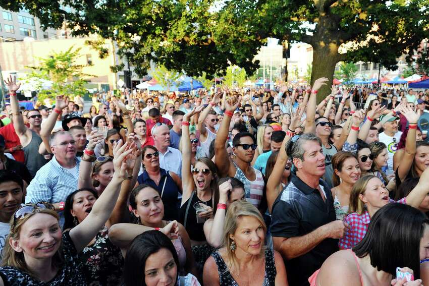 The packed crowd at Columbus Park put their hands in the air during the Alive@Five headliner Easton Corbin's performance on Thursday, August 4, 2016.