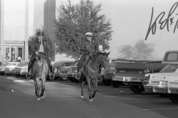 11/25/1983 - Houston Police mounted officers patrol Greenspoint Mall parking lot on horseback.