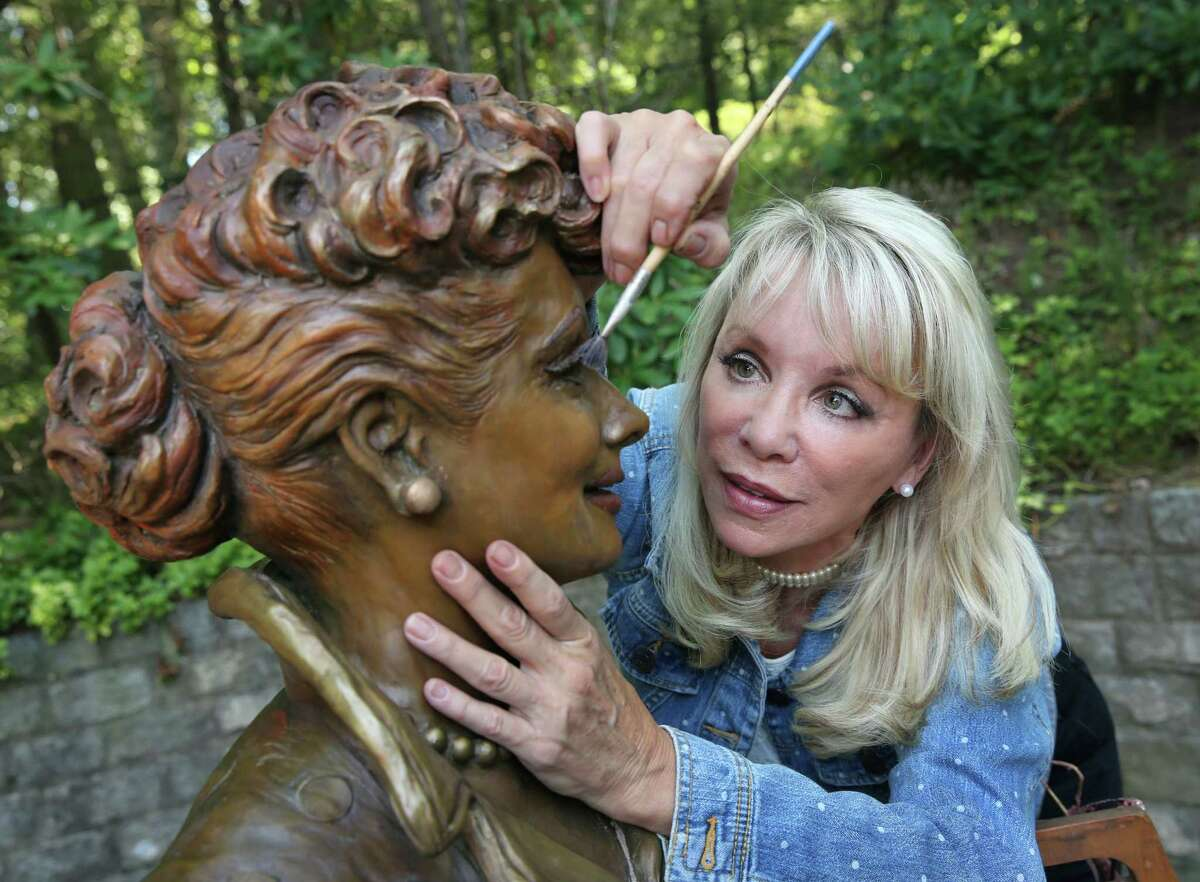 In this Wednesday, July 20, 2016 photo, artist Carolyn Palmer prepares to apply a cold patina to her bronze statue of Lucille Ball in Saddle River, N.J. The sculptor was chosen to create a replacement statue for one dubbed