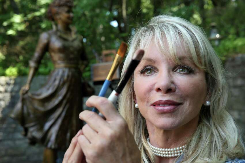 In this Wednesday, July 20, 2016 photo, artist Carolyn Palmer compares brushes as she prepares to apply a cold patina to details on her bronze statue of Lucille Ball in Saddle River, N.J. The sculptor was chosen to create a replacement statue for one dubbed