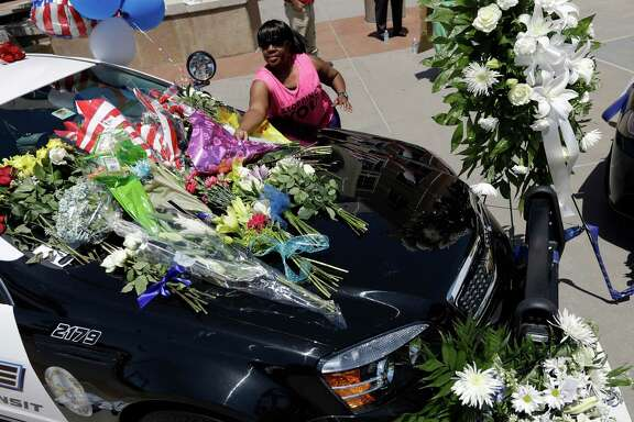FILE - In this Friday, July 8, 2016 file photo, Cynthia Ware places flowers on a make-shift memorial at the Dallas police headquarters, in Dallas. Five police officers are dead and several injured following a shooting in downtown Dallas Thursday night.  (AP Photo/Eric Gay, File)