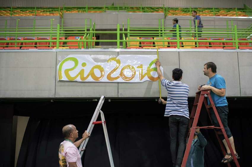 Workers install a Rio 2016 logo at the Riocentro venue in Rio de Janeiro on August 4, 2016, ahead of the Rio 2016 Olympic Games. / AFP PHOTO / Ed JONESED JONES/AFP/Getty Images