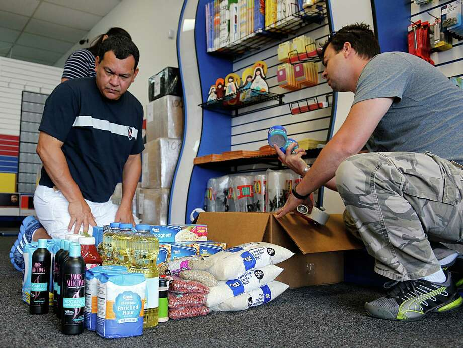 Yersys Rivas, left, and Jhimy Gelabert are ship-ping food and hygiene items to kin in Venezuela. Photo: James Nielsen, Staff / © 2016  Houston Chronicle