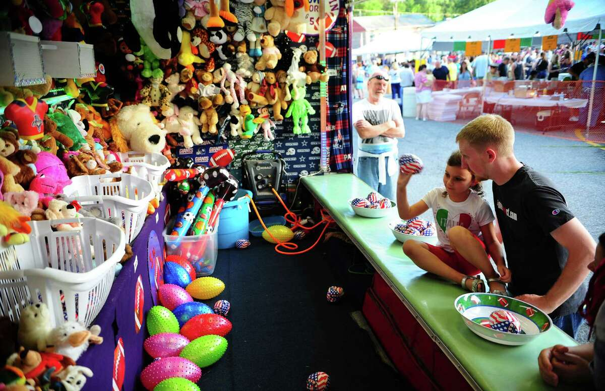 Liliana Bedna, 5, plays on of the games of chance with her dad Robert at Festa! 2016: Holy Rosary Church's 49th Annual Ansonia Italian Festival on the church grounds in Ansonia, Conn., on Thursday Aug. 4, 2016. The festival runs through Saturday Aug. 6 from 5 p.m. to 10 p.m. The festival features Italian food and deserts, live music each night and carnival rides for the kids.