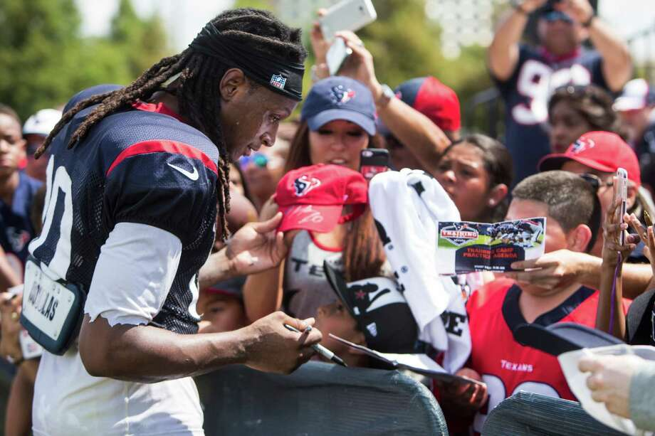 Texans fans eagerly seek the autograph of wide receiver DeAndre Hopkins during training camp Thursday. Hopkins, who held out for one day seeking a pay raise, received a tidy little bonus check Thursday. Photo: Brett Coomer, Staff / © 2016 Houston Chronicle