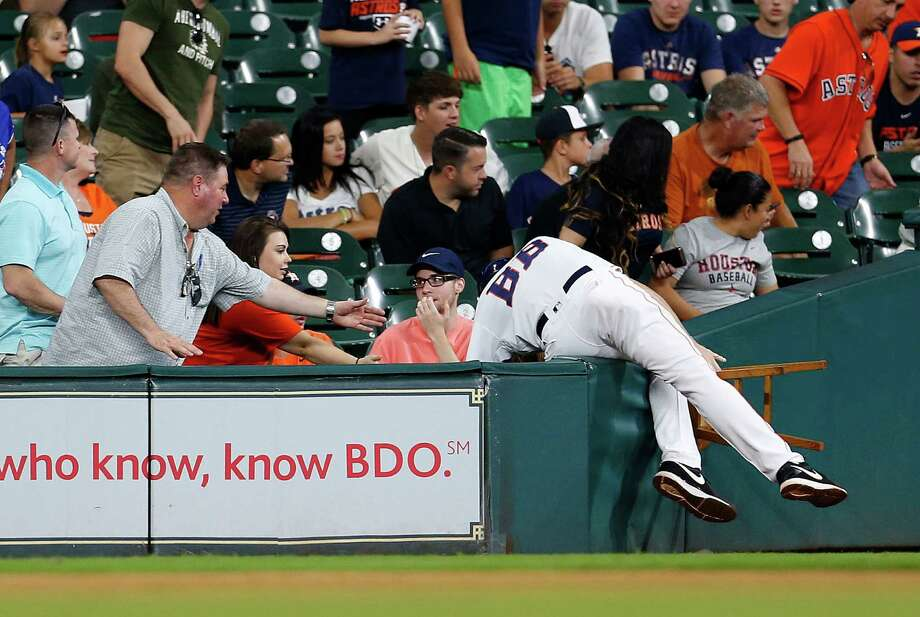 A bat boy flies into the stands after chasing a foul ball during the eighth inning of an MLB game at Minute Maid Park, Thursday, Aug. 4, 2016, in Houston. Photo: Karen Warren, Houston Chronicle / © 2016 Houston Chronicle