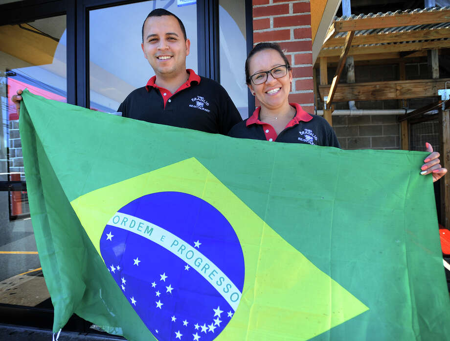Dangelo Fernandes and his wife Denia Maciel hold a Brazilian flag outside their Terra Brasilis Restaurant on North Avenue in Bridgeport, Conn. on Thursday, August 4, 2016. Fernandes said they plan to show television coverage of the Olympic Games, this year in Brazil, on a large drop down screen in the restaurant. Photo: Brian A. Pounds / Hearst Connecticut Media / Connecticut Post