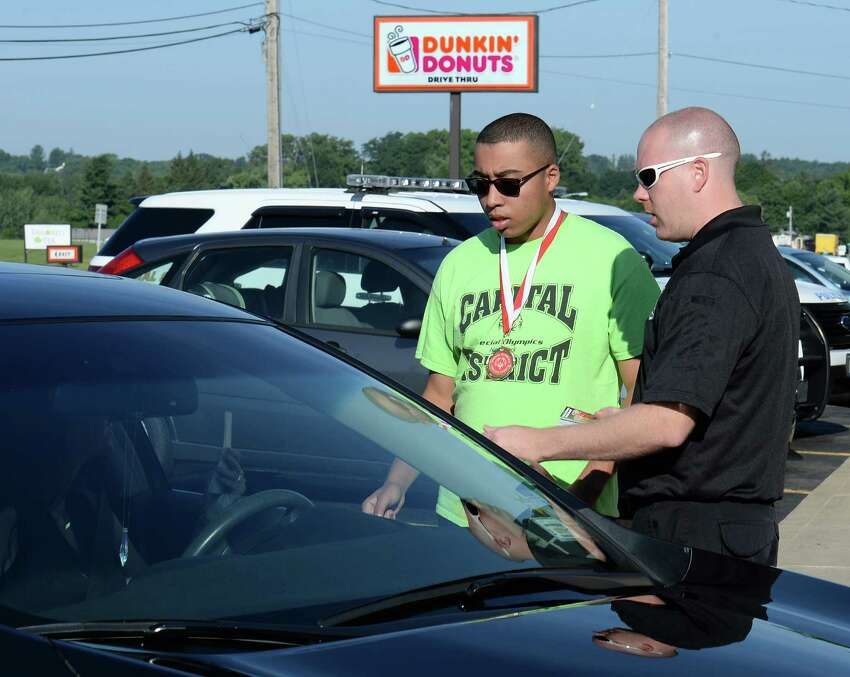 Special Olympics athlete Anthony Lawless, left, of Colonie and Nick Gingeresky from the Albany County Sheriff's Dept. speak with a DunkinO Donuts customer during the annual Cops on Top event to raise awareness and funds for Special Olympics New York at the Troy Schenectady Road store Friday Aug. 5, 2016 in Colonie, NY. (John Carl D'Annibale / Times Union)
