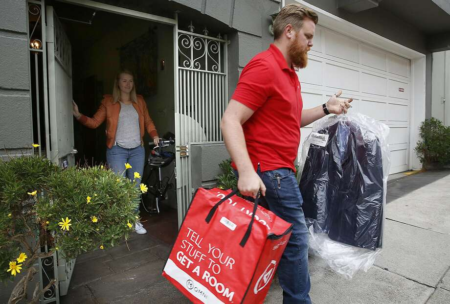 Ryan Galligan of Omni picks up items including a suit from Julie Kaas last week in San Francisco. Omni is an on-demand storage firm that offers pickup and delivery, so customers do not need to cram items into units. Photo: Liz Hafalia, The Chronicle