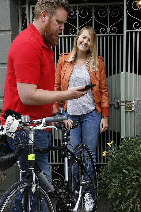 Julie Kaas gives a bike to Omni concierge Ryan Galligan last week in San Francisco. Omni is an on-demand storage concierge service company that offers pickup and delivery solutions. Photo: Liz Hafalia, The Chronicle