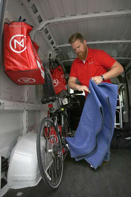 Ryan Galligan of Omni places a bike in his truck after picking up items in San Francisco. The startup offers pickup and delivery service for customers, who pay monthly storage fees. Photo: Liz Hafalia, The Chronicle