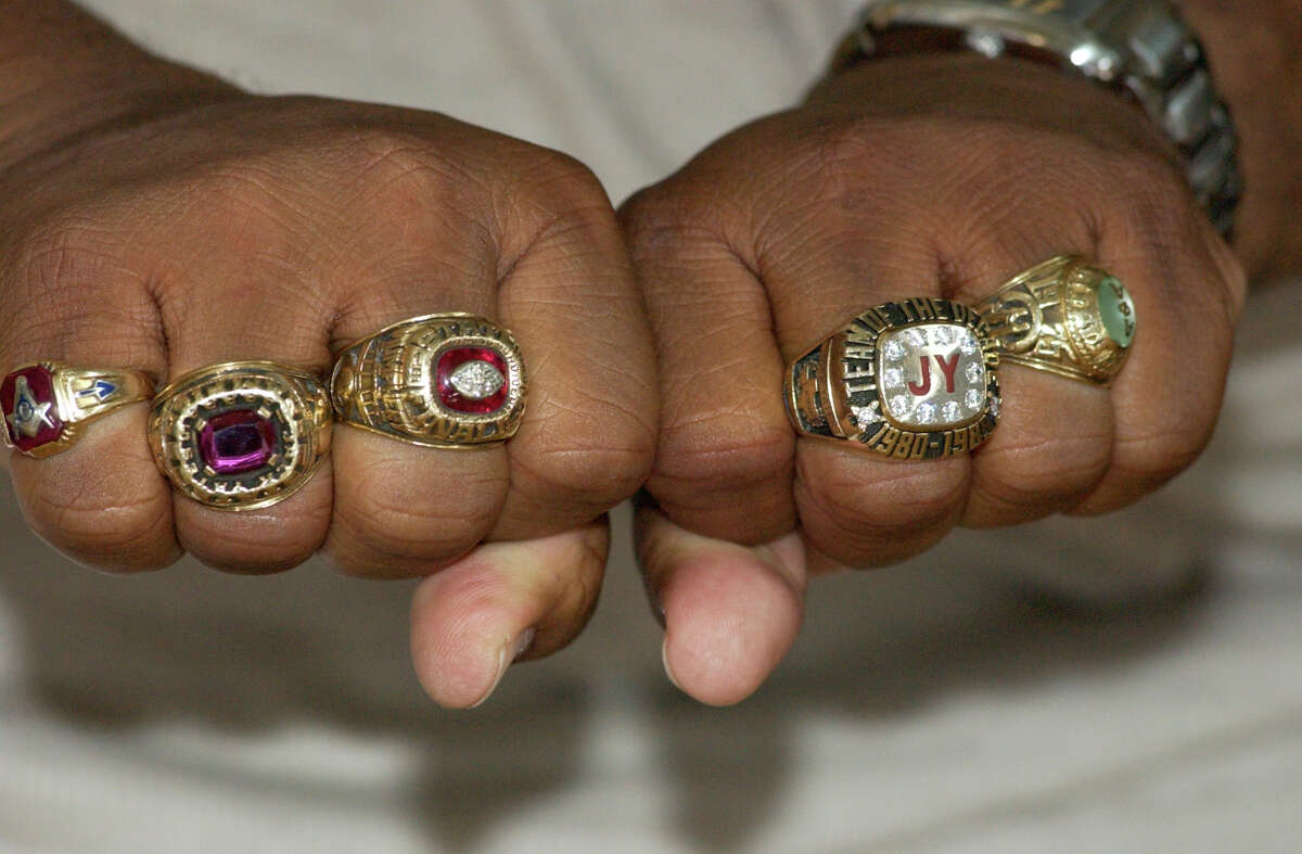 Former assistant coach Ronald Mumphery (CQ) of the 1985 Yates State Championship football team, displays 1985 championship ring, second from left, 1992 championship ring, third from left, and the a diamond encrusted Team of the decade ring for the 1980s. Mumphery, currently principal at Cullen Middle School hosted a charity basketball game between teams of 1985 and 1986 alumni, Saturday May 21, 2005 at Cullen Middle School. Members of that championship team who went on to NFL careers include Quinton Smith, Charles Price, Zeno Alexander and James Good. Yates alumni are rallying around their school, recently in the news for poor academic performance. Chronicle/Ben DeSoto HOUCHRON CAPTION (05/29/2005) SECNEWS COLORFRONT: PRIDE: Ronald Mumphery, now principal at Cullen Middle, displays rings from his time at Yates, including his 1985 Class 5A title ring, second from left, and a Team of the Decade ring, second from right.