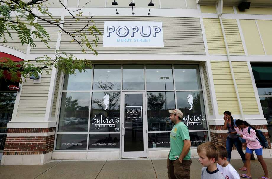 People walk past the entrance to a pop-up store location at the Derby Street Shoppes outdoor mall, in Hingham, Mass. Entrepreneurs increasingly are taking the pop-up concept in new and unexpected directions. Photo: Steven Senne /Associated Press / Copyright 2016 The Associated Press. All rights reserved. This material may not be published, broadcast, rewritten or redistribu