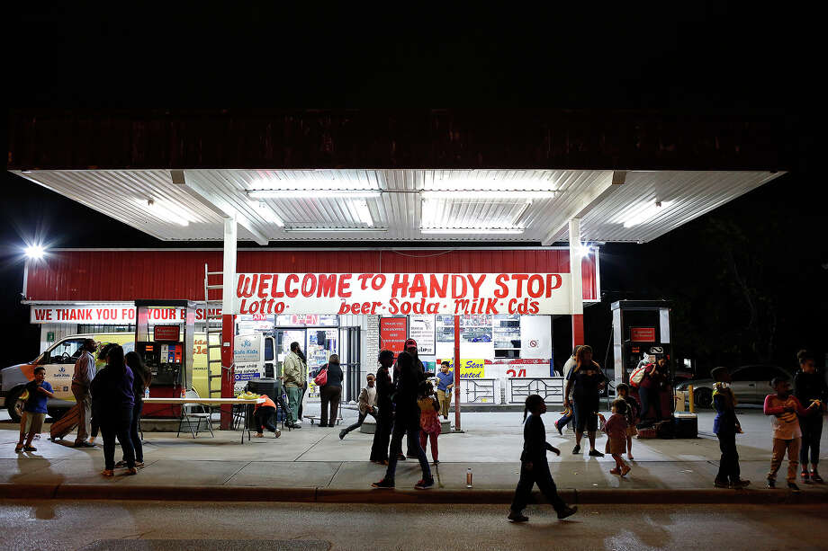 Area residents mill about as the harvEAST Festival and Community Block Party winds down outside the Handy Stop Convenience Store on N. New Braunfels on Friday, Nov. 13. Photo: Lisa Krantz / Lisa Krantz / SAN ANTONIO EXPRESS-NEWS