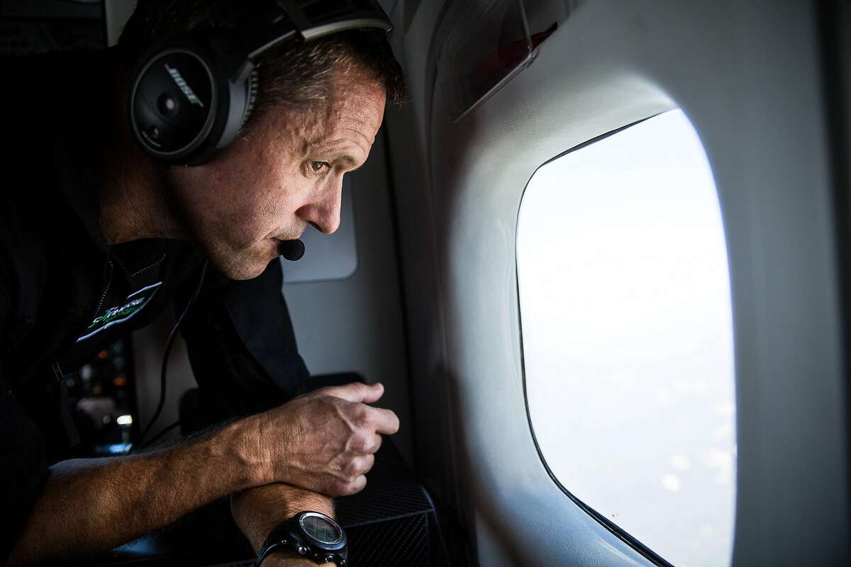 Scientist Greg Asner peers out a window during a flight to map tree health in the Sierras, July 27, 2016.