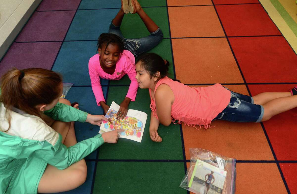 Norwalk Public Schools Summer reading program students, Chedeline Lavaze and Michelle Correno ,work with Teacher's Assistant, Melissa Burham, during the program at Naramake Elementary School Tuesday, July 12, 2016. in Norwalk, Conn.