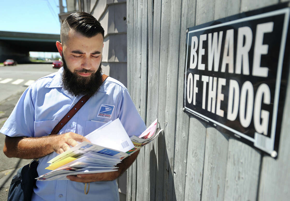 Bridgeport mail carrier Raul Ruiz delivers mail on foot during his daily route on the East Side of Bridgeport, Conn. on Wednesday, August 3, 2016. Ruiz said he tries to make friends with the dogs on his route, and to this point hasn't been bitten.