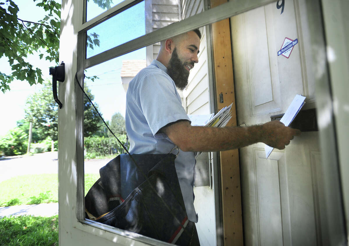 Bridgeport mail carrier Raul Ruiz delivers mail on foot during his daily route on the East Side of Bridgeport, Conn. on Wednesday, August 3, 2016. Ruiz said he is careful not to put his fingers through a door's mail slot, where they can be bitten by dogs.