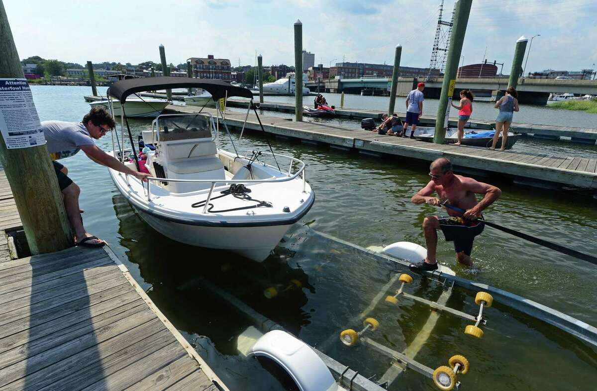 Norwalk resident Dennis Brown, right, and his son, Robert Brown, launch their boat at the Norwalk Visitors Dock at Veteran's Memorial Park in Norwalk on Friday, Aug. 5.