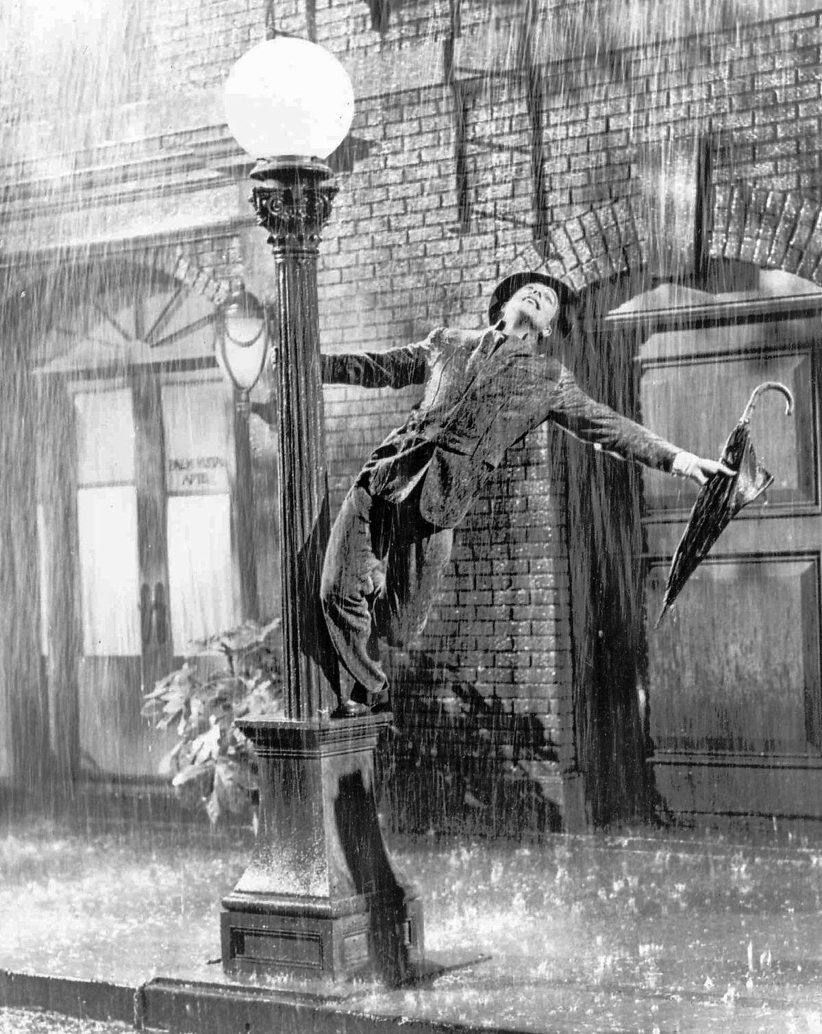 FILE - Gene Kelly performs in the 1952 film ``Singin' in the Rain''. Kelly, a dancer and choreographer who brought his athletic grace and Irish charm to ``Singin' in the Rain and other great movie musicals of the 1940s and '50s, died Friday, Feb. 2, 1996 at his Beverly Hills home his publicist said. Kelly's most memorable dance was the title number of ``Singin' in the Rain,'' in which he splashed joyously through puddles on a near-deserted street, his love for Debbie Reynolds rendering him oblivious to the wet. (AP Photo, files)