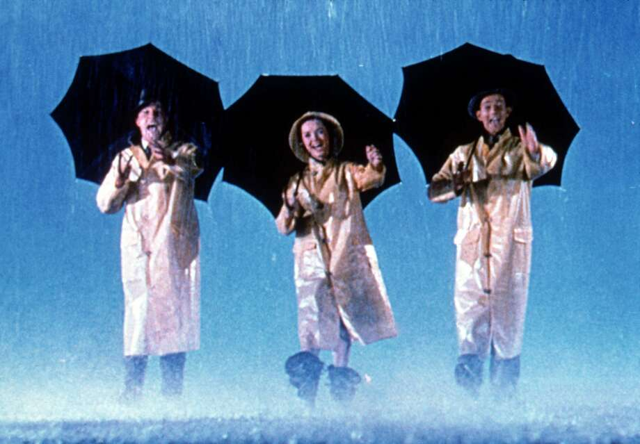 "Gene Kelly, Debbie Reynolds and Donald O'Connor in ""Singin' in the Rain."" Full shot of illustration of Gene Kelly as Don Lockwood, Debbie Reynolds as Kathy Selden, and Donald O'Connor as Cosmo Brown walking together in rain, holding umbrellas during the opening musical number ""Singin' In The Rain."" Photo: MGM 1952"