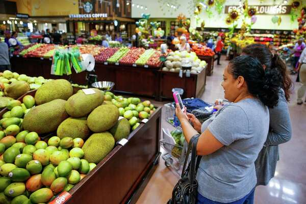 Maria Alcatraz takes  a photo of the produce at the  new Kroger. She said  she was  going to  send the photo to her father in Mexico.