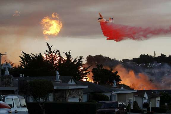 FILE - In this Sept. 9, 2010, file photo, a massive fire following a pipeline explosion roars through a mostly residential neighborhood in San Bruno, Calif. In a big victory for Pacific Gas & Electric Co., a judge has cut nearly all of a potential $562 million fine against the giant utility in a criminal case alleging it violated safety regulations before a deadly natural gas pipeline explosion in California and then obstructed investigators. (AP Photo/Jeff Chiu, File)