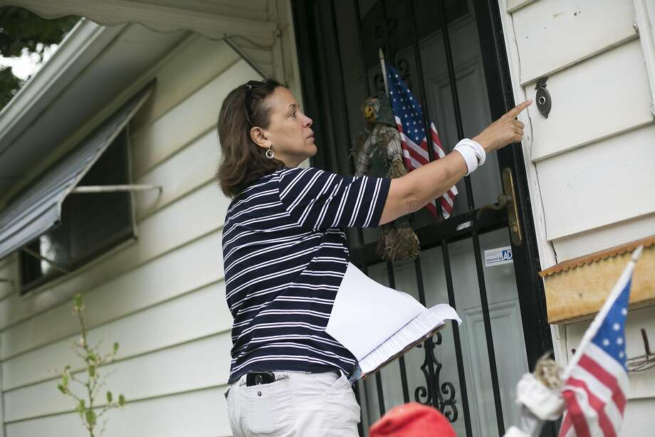 Darleen Tinsley rings a doorbell while canvassing for Hillary Clinton in Cleveland. Photo: Maddie McGarvey, Special To The Chronicle