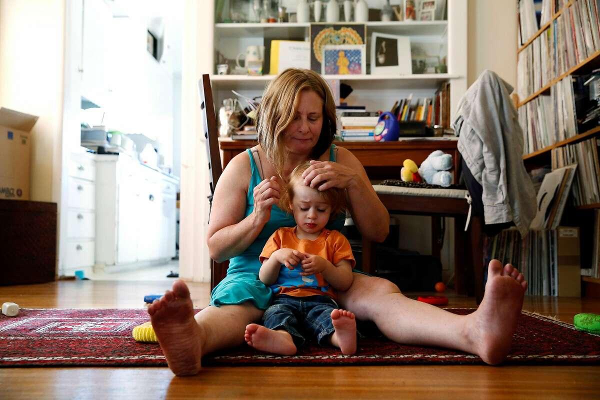 Alyson Kohn brushes aside her son Julian Black's hair at their home in Emeryville, California, on Monday, August 1, 2016.