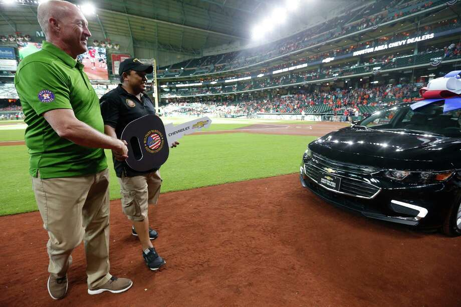 Bill Suessman, President of theHouston Area Chevy Dealers, points U.S. Army Specialist Christopher Sum in the direction of his brand new, 100 percent payment-free Chevrolet Malibu, just before throwing out the first pitch of the game before the start of an MLB game at Minute Maid Park, Friday, Aug. 5, 2016, in Houston. Photo: Karen Warren, Houston Chronicle / © 2016 Houston Chronicle