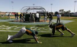 Yoenis Cespedes (left) stretches with conditioning coach Mike Henriques before his first workout at the Oakland A's camp in Phoenix, Ariz. on Sunday, March 4, 2012. Cespedes, who defected from Cuba last year, signed a four-year contract with Oakland.