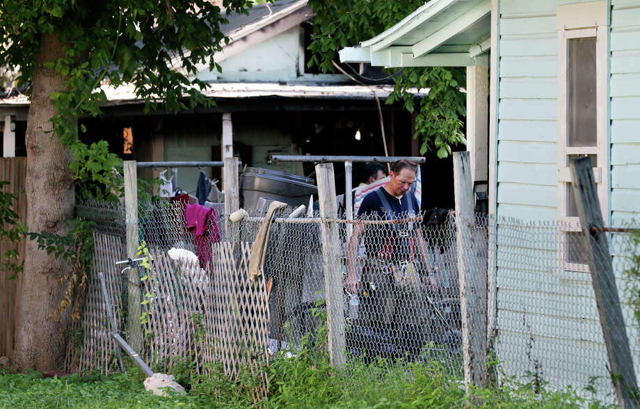 A fire fighter looks through the yard of a house on Green Street where at least one person died in a fire August 5, 2016 Photo: SAN ANTONIO EXPRESS-NEWS / 2016 SAN ANTONIO EXPRESS-NEWS
