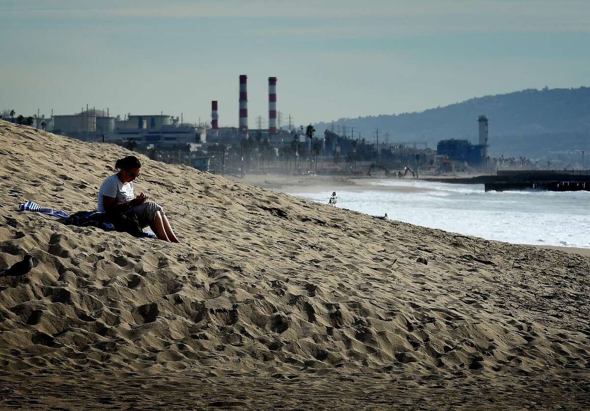 A woman sits on a sand berm created by city workers to protect houses from El Nino storms and high tides at Playa Del Rey beach in Los Angeles, California on November 30, 2015, at the start of the COP21 conference in Paris. Some 150 leaders, including US