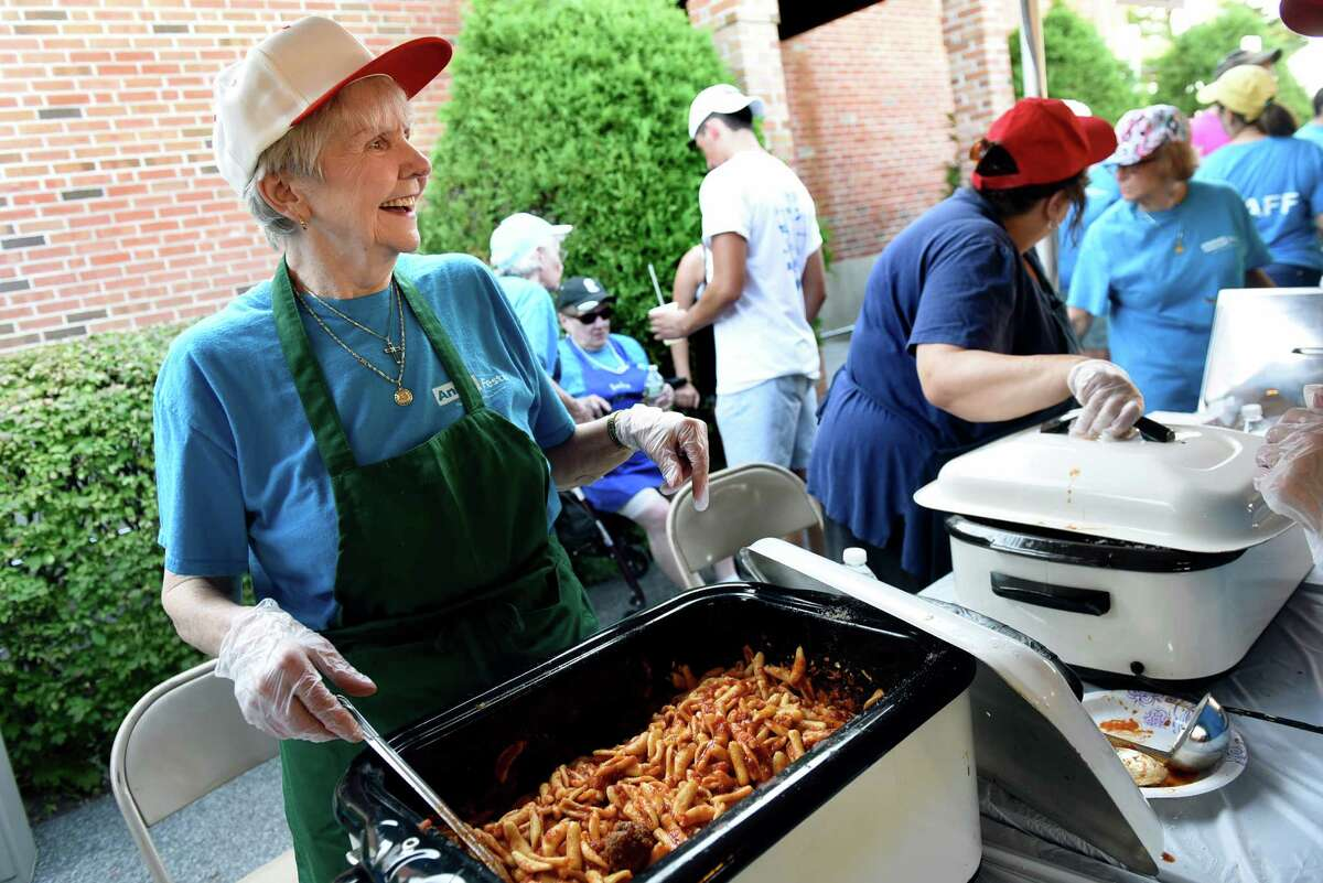 Church member Phyllis Johnson, left, serves cavatelli, either with or without meatballs, during the annual Festa on Friday, Aug. 5, 2016, at Our Lady Queen of Peace in Rotterdam, N.Y. The event features Italian food, music, rides and games and continues Saturday from 5 to 11 p.m. and Sunday from 3 to 9 p.m. (Cindy Schultz / Times Union)