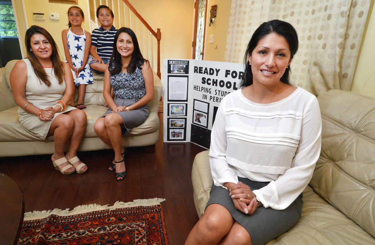 Yessenia Martinz, founder and director of Ready for School, with Esmeralda DeLaCruz, volunteer coordinator, and Yessica Zucca, secretary and board member, and Natalia Martinez with Santiago Zucca all on the couch. Ready for School is a local nonprofit that raises money through donations to help students in some of the poorest areas of the country.