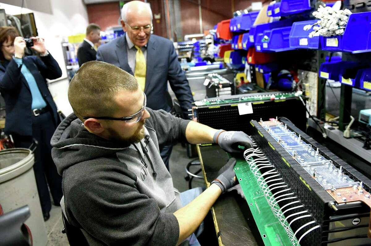 Production technician Josh Bellow, center, solders a circuit board to a battery as Rep. Paul Tonko, right, tours the plant on Tuesday, Feb. 16, 2016, at Plug Power in Latham, N.Y. (Cindy Schultz / Times Union)