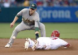 ANAHEIM, CA - AUGUST 2: Jed Lowrie #8 of the Oakland Athletics takes the throw from catcher Stephen Vogt #21 of the Oakland Athletics to throw out Mike Trout #27 of the Los Angeles Angels of Anaheim at second base during a steal attempt during the first inning of the baseball game at Los Angeles Angels of Anaheim at Angel Stadium of Anaheim August 2, 2016, in Anaheim, California. (Photo by Kevork Djansezian/Getty Images)