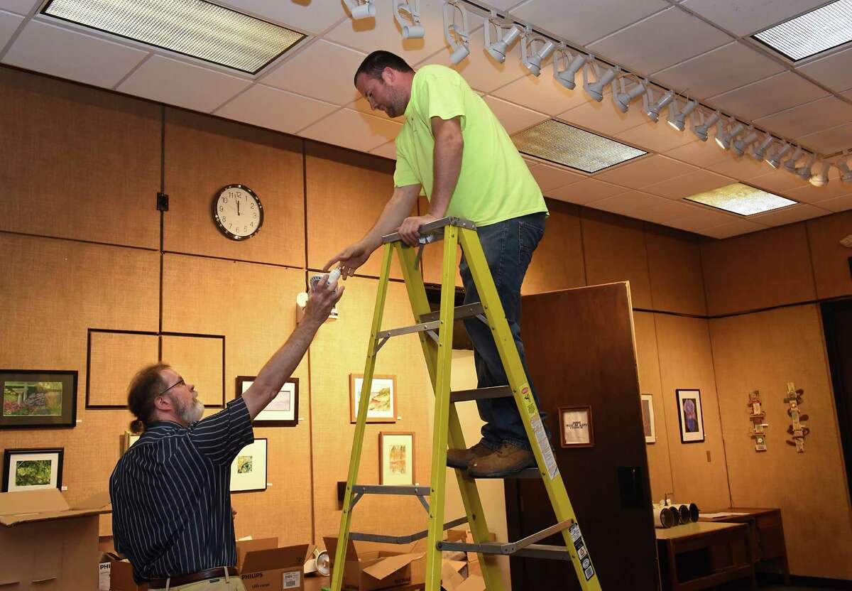 Library assistant Greg Rucinski, left, hands a lightbulb to senior custodial worker Shaun Soucy who is installing new lighting in the main meeting room at the William K. Sanford Library on Wednesday Aug. 3, 2016 in Colonie, N.Y. The library has decided to spend $1-3 million on renovations. (Lori Van Buren / Times Union)
