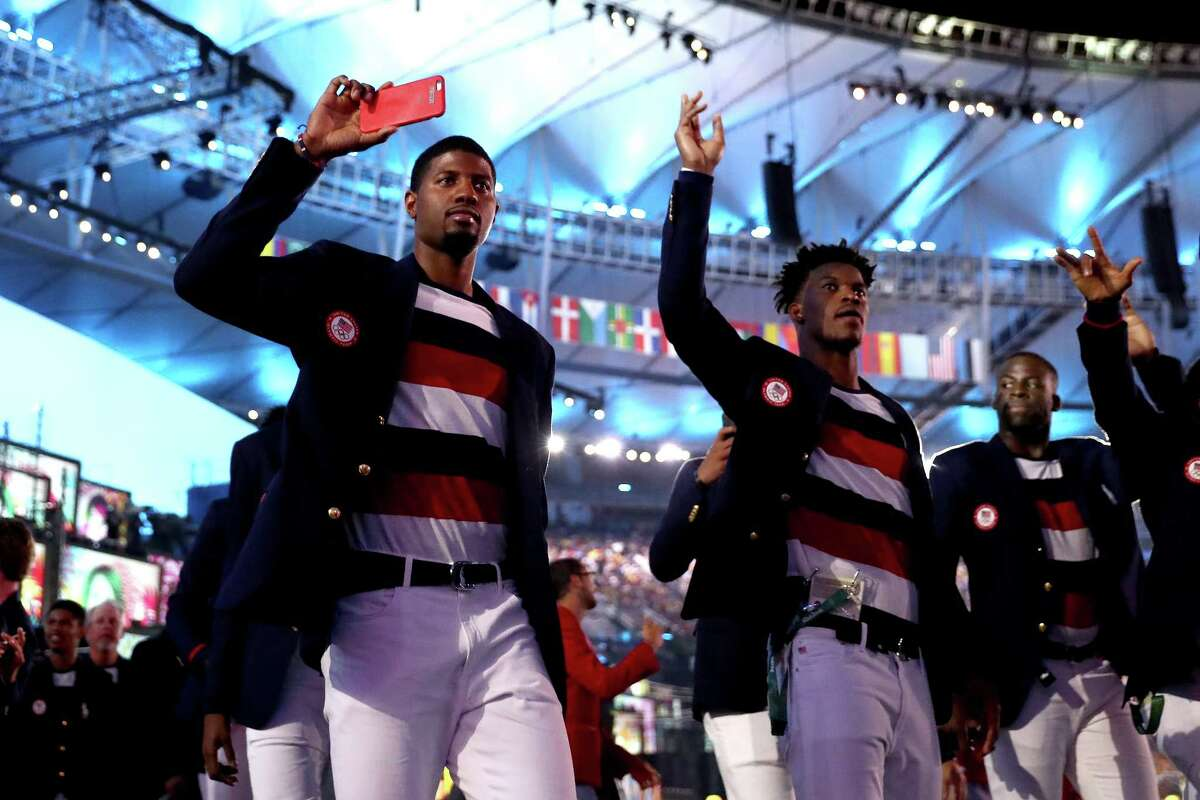 RIO DE JANEIRO, BRAZIL - AUGUST 05: Paul George (L) and Jimm Butler (C) of the United States enter the stadium during the Opening Ceremony of the Rio 2016 Olympic Games at Maracana Stadium on August 5, 2016 in Rio de Janeiro, Brazil. (Photo by Ezra Shaw/Getty Images) ORG XMIT: 595885125